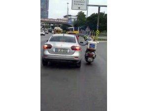 Arızalanan motosikletiyle otomobilin camına tutunup seyahat eden motosikletli kamerada