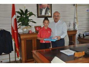 Türkiye Şampiyonu tekvandocu Yangın, İlçe Milli Eğitim Müdürü Mahmut Demir'i ziyaret etti