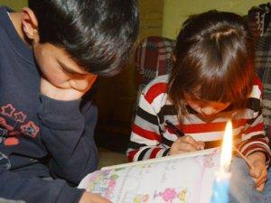 Mum ışığında ders çalışıp ödev yapıyorlar