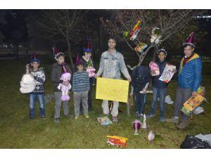 Savaşlara dikkat çekmek için, ağaç süsleyip çocuklara oyuncak dağıttı