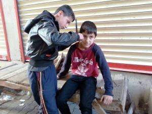 Cizre'de 13 yaşındaki berber, kapı önünde arkadaşlarını traş ediyor