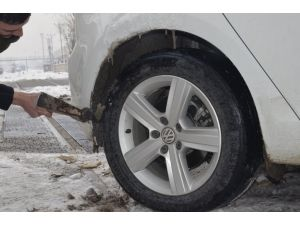 Tampon ve tekerlek arasına sıkışan buzu kazma ile kırdı