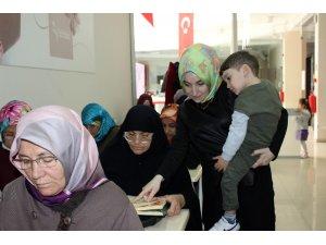 Kucağında çocuğu elinde kalemi öğrencilere ders veriyor