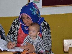 Kucaklarında bebekleri ile okuma yazma öğreniyorlar