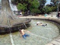 Sıcaktan bunalan çocuklar süs havuzunda yüzerek serinledi