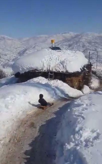 Köylü çocuklar, karla kaplı köy yolunu kayak yoluna çevirdi